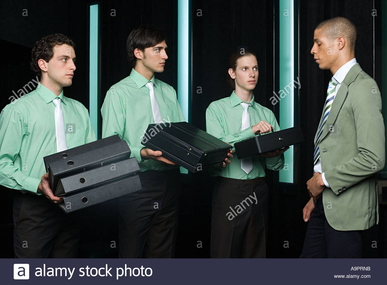 Office workers handing items to manager - Stock Image