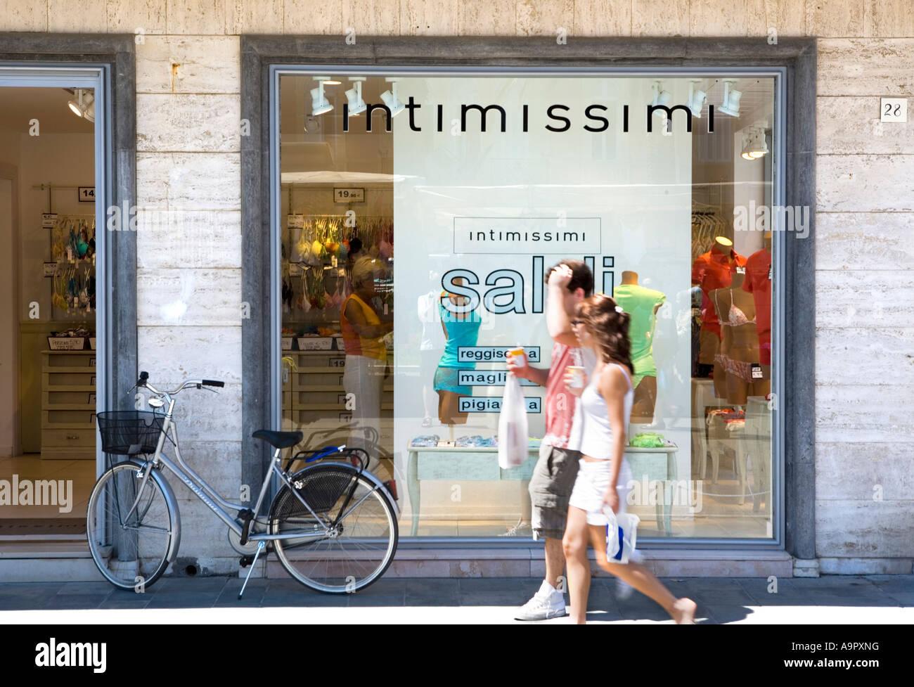 Bicycle passers by and shop Viareggio Tuscany Coast Italy - Stock Image