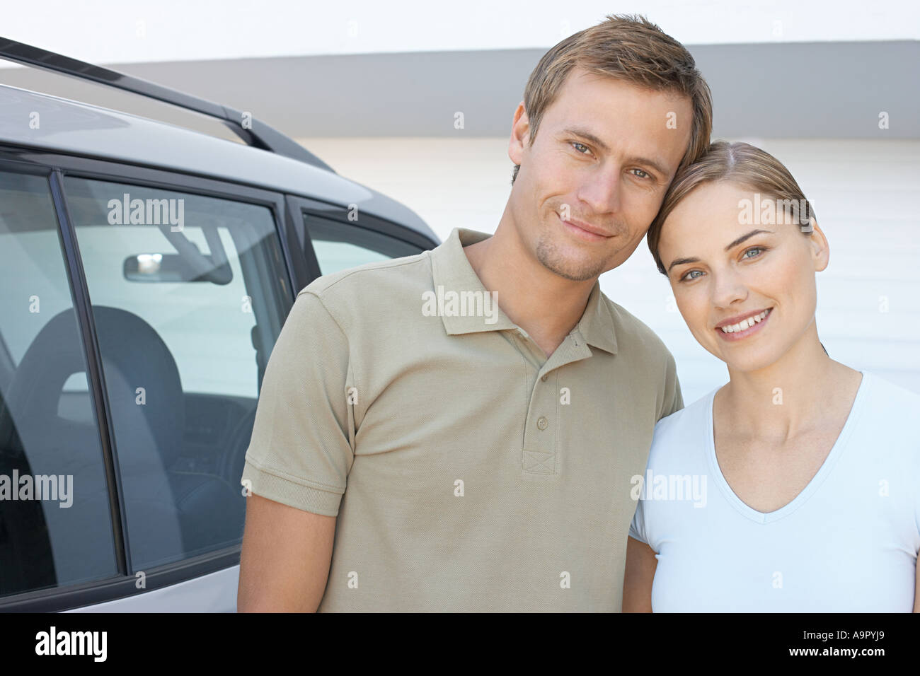 Mid adult couple stood outside with car - Stock Image