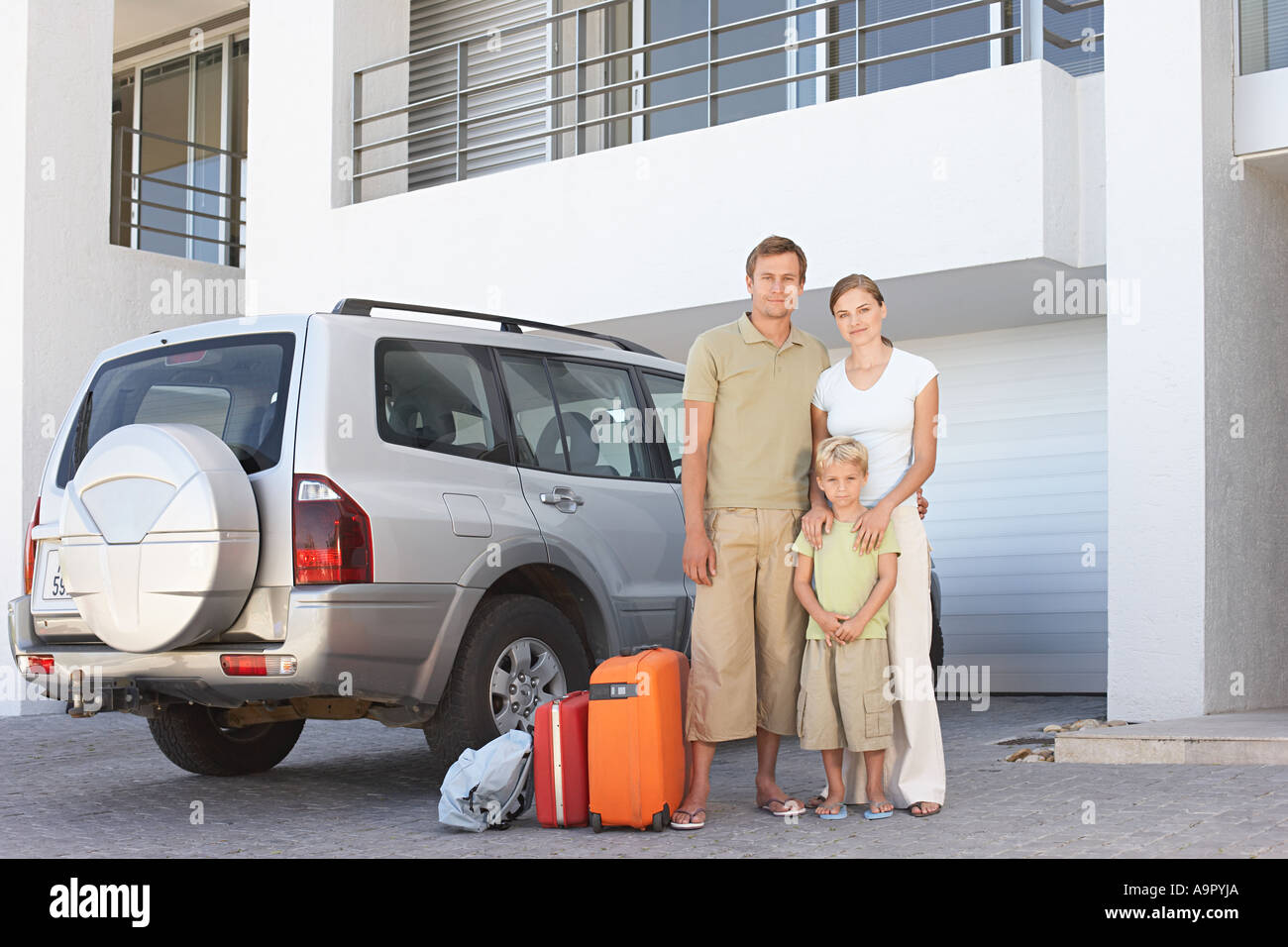 Family stood by car with suitcases - Stock Image