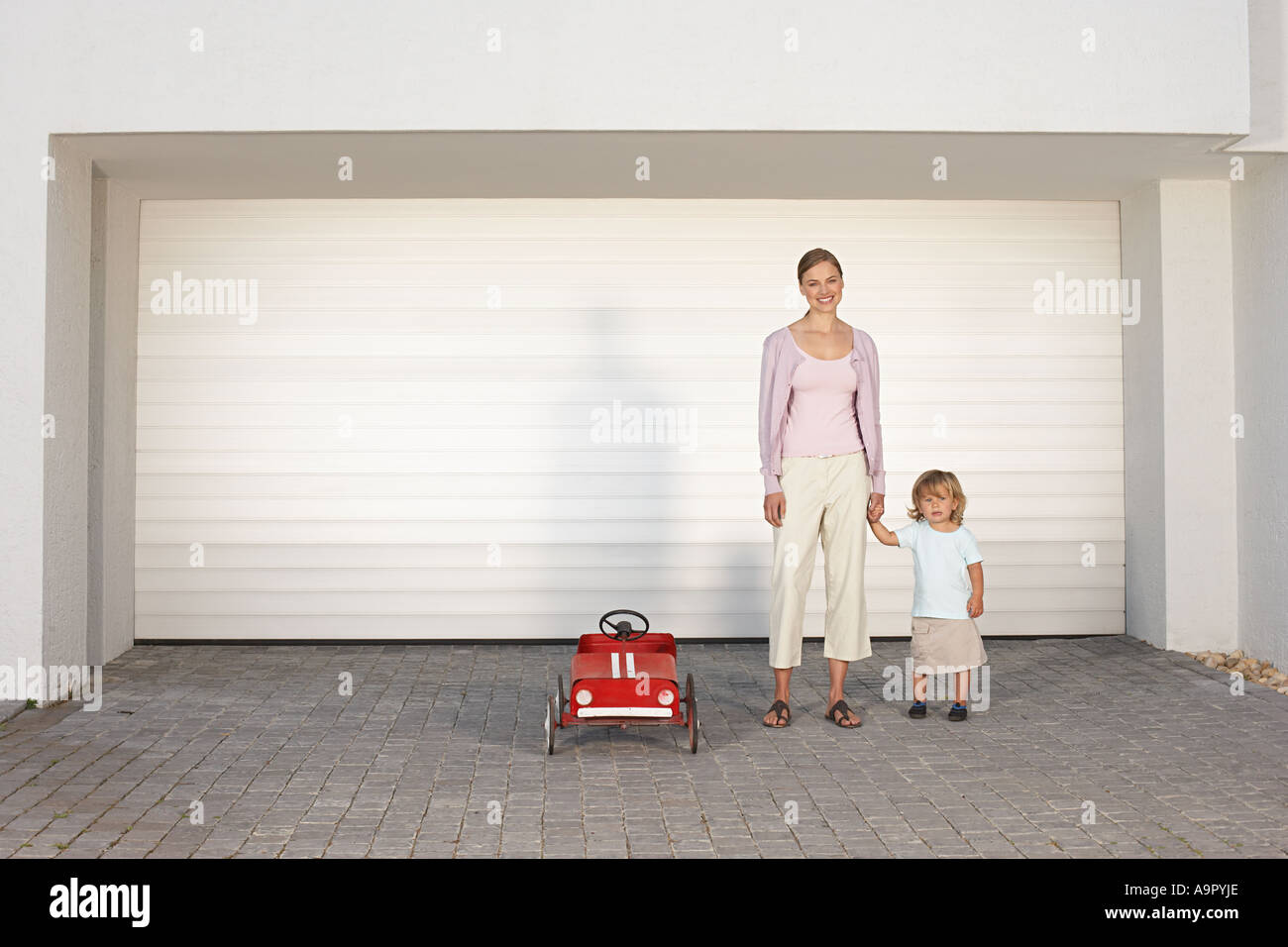 Mother and daughter stood in driveway - Stock Image