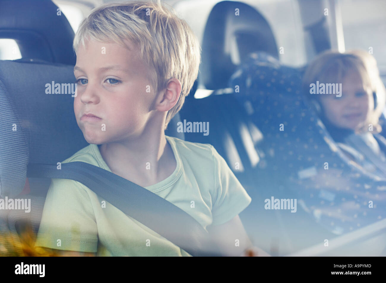 Two children sat in the back of car - Stock Image