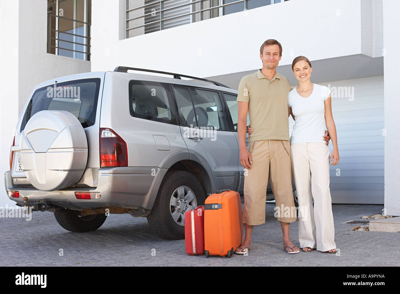 Couple stood by car with suitcases - Stock Image