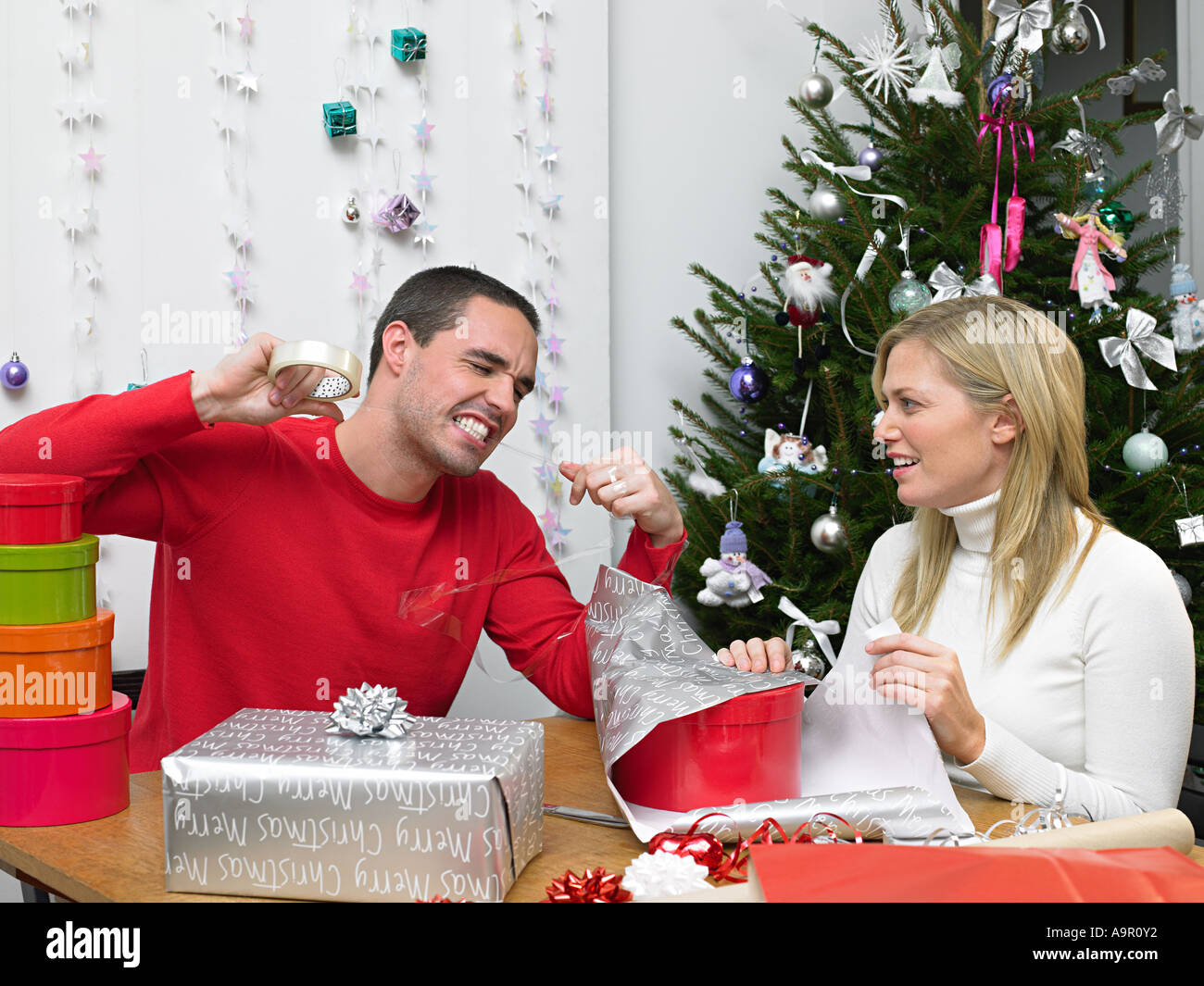 Couple wrapping christmas presents - Stock Image