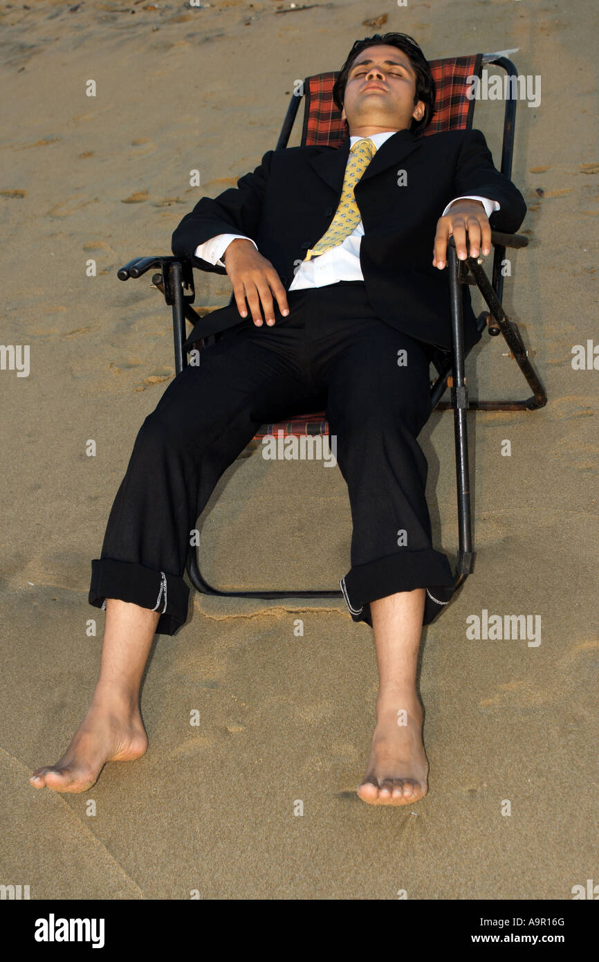 A businessman sitting on a beach - Stock Image