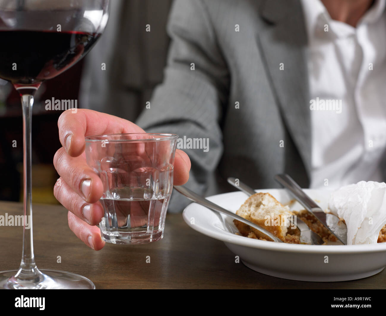 Man sitting with glass of water and finished meal - Stock Image