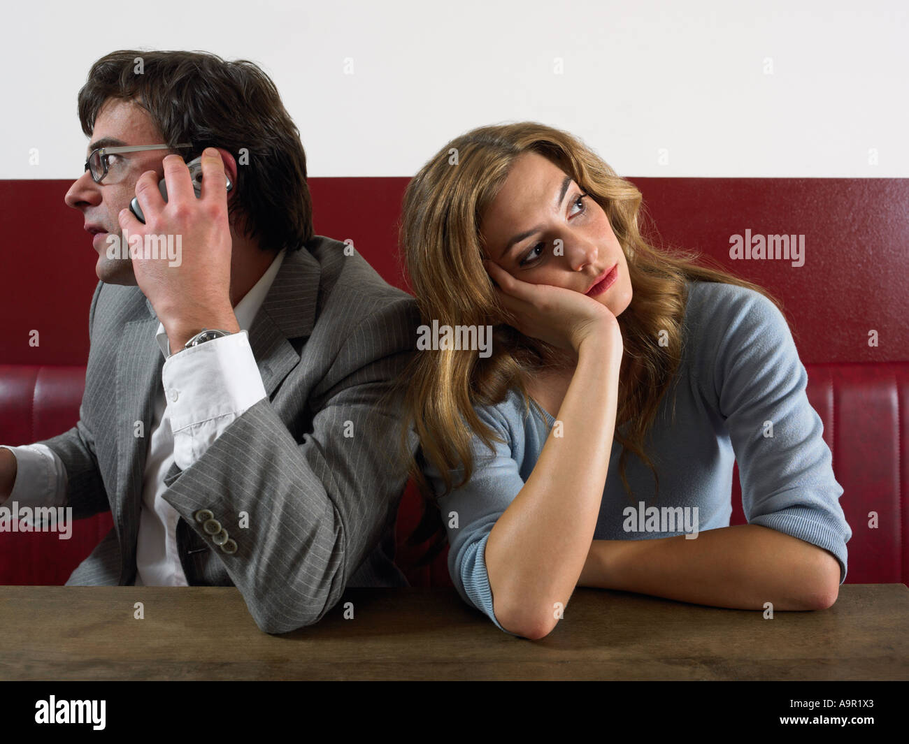 Woman bored as man talks on phone - Stock Image