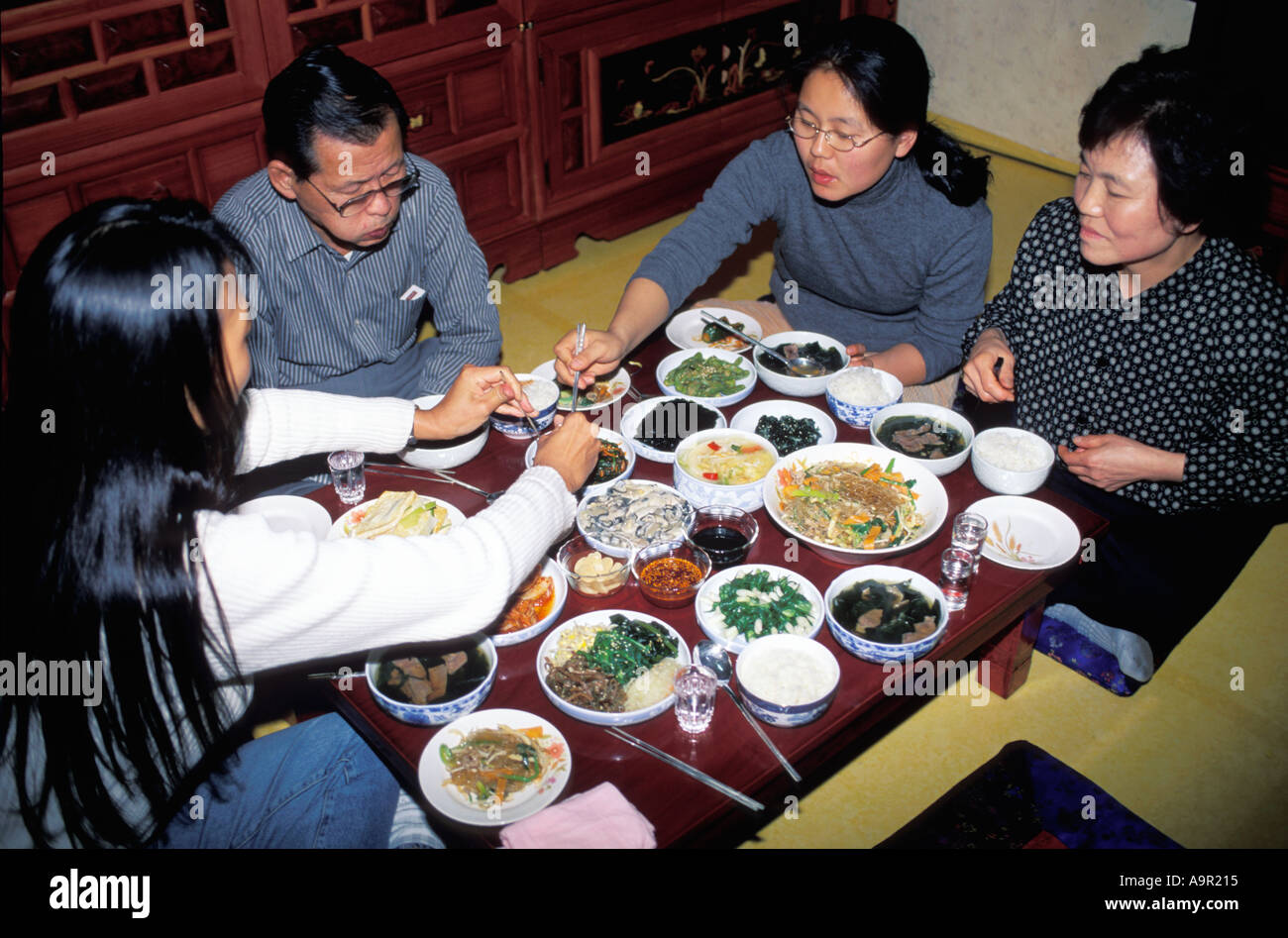 Korean family eating traditional food in typical home setting Stock Photo