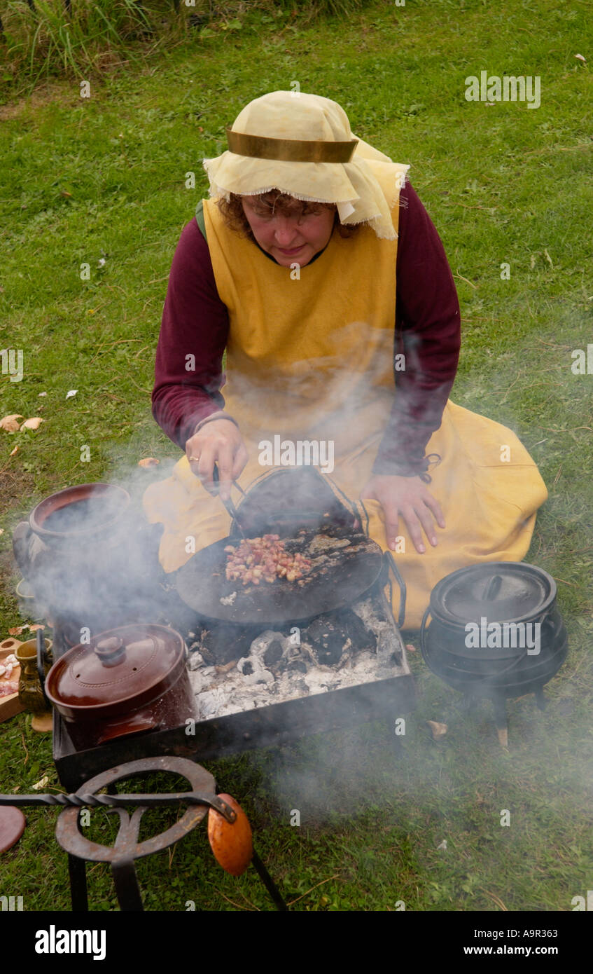 Medieval cook cooking outside on open fire at the annual Abergavenny Food Festival Monmouthshire South Wales UK - Stock Image