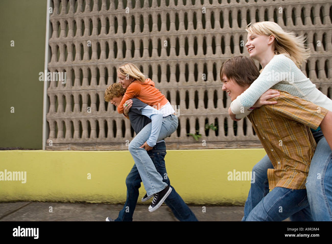 Four teenagers running piggy back races - Stock Image