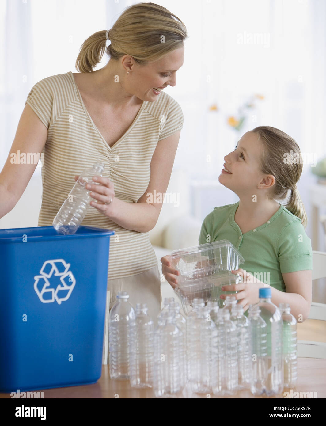 Mother and daughter filling recycle bin - Stock Image