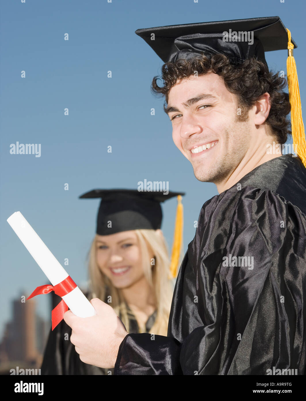 Man wearing graduation cap and gown with diploma Stock Photo ...