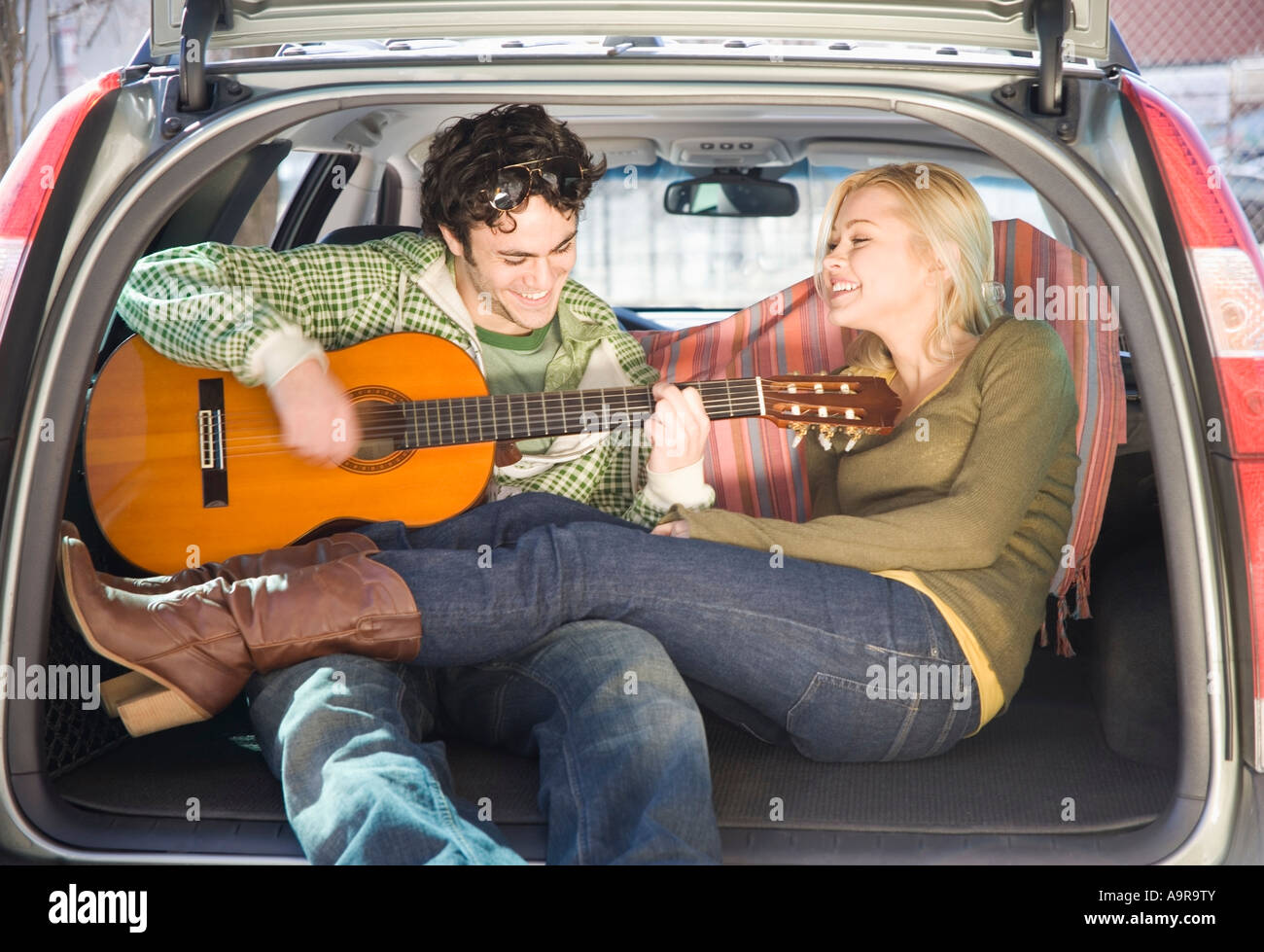 Couple sitting in back of car with guitar - Stock Image