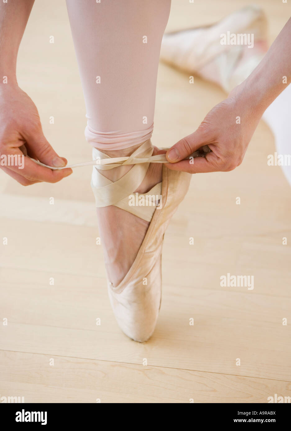 Female ballet dancer tying pointe shoes - Stock Image