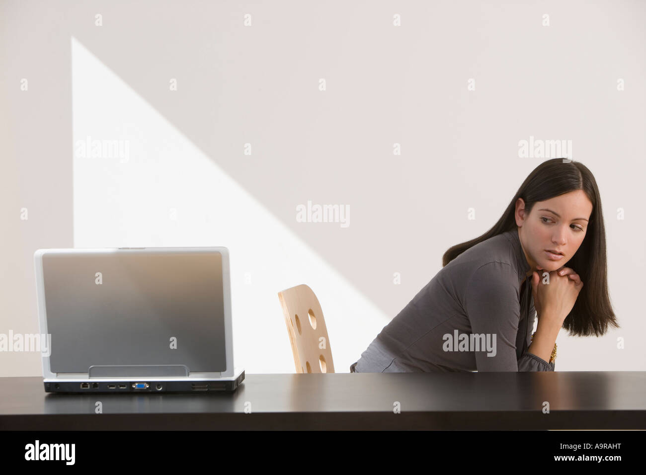Woman looking over shoulder at laptop - Stock Image