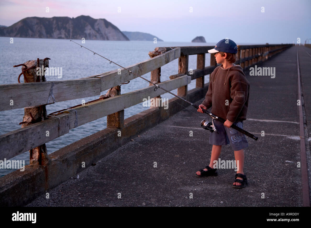boy 6 fishing in the evening of wharf at tolaga bay - Stock Image