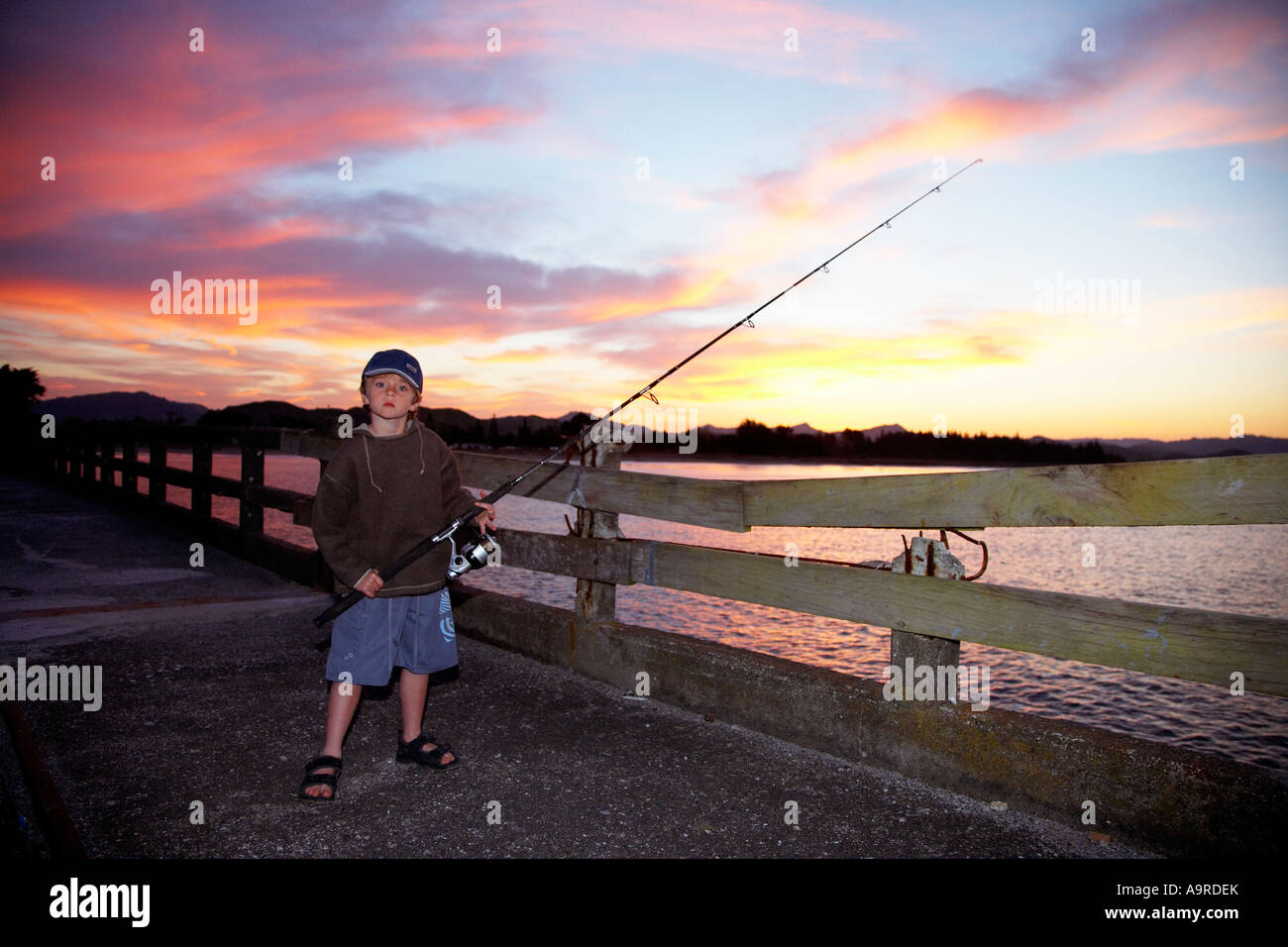 boy 6 fishing in the evening of wharf at tolaga bay with sunset behind him - Stock Image