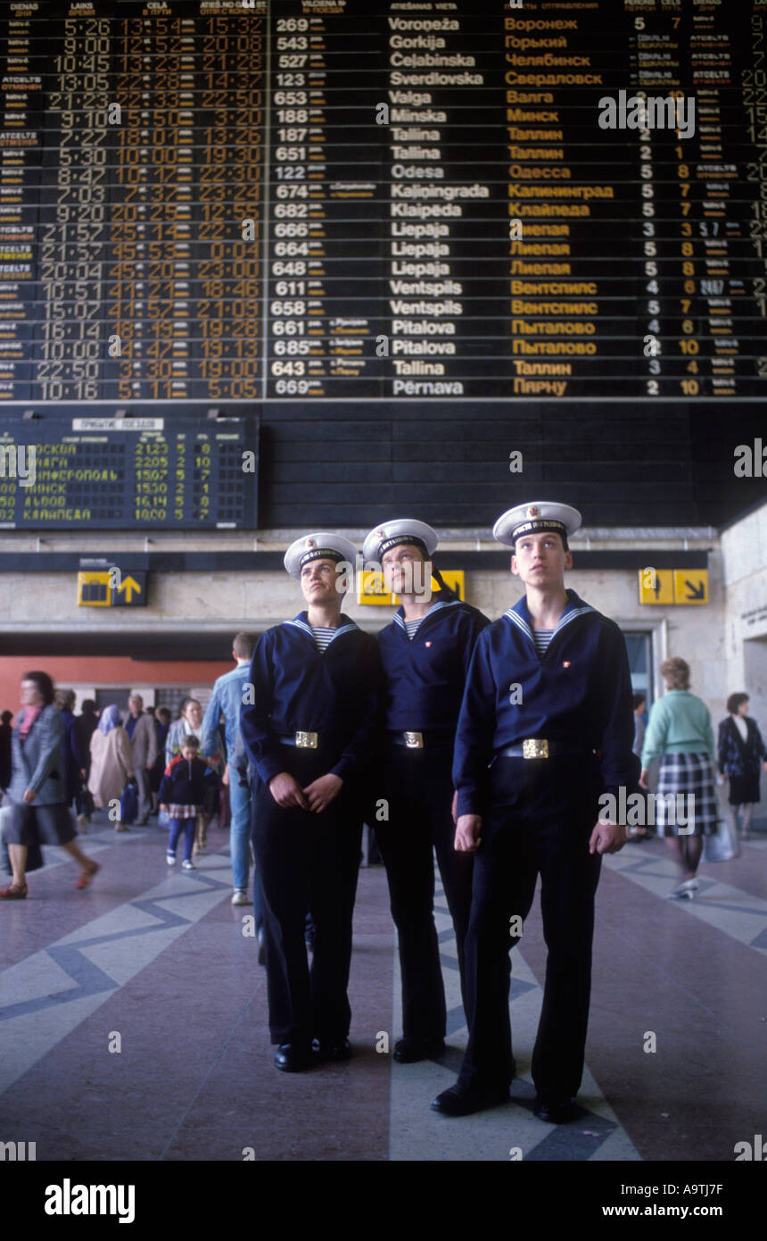 Riga Latvia 1980s  Three young male sailors in their uniform look up at a railway train notice board Central railway Stock Photo