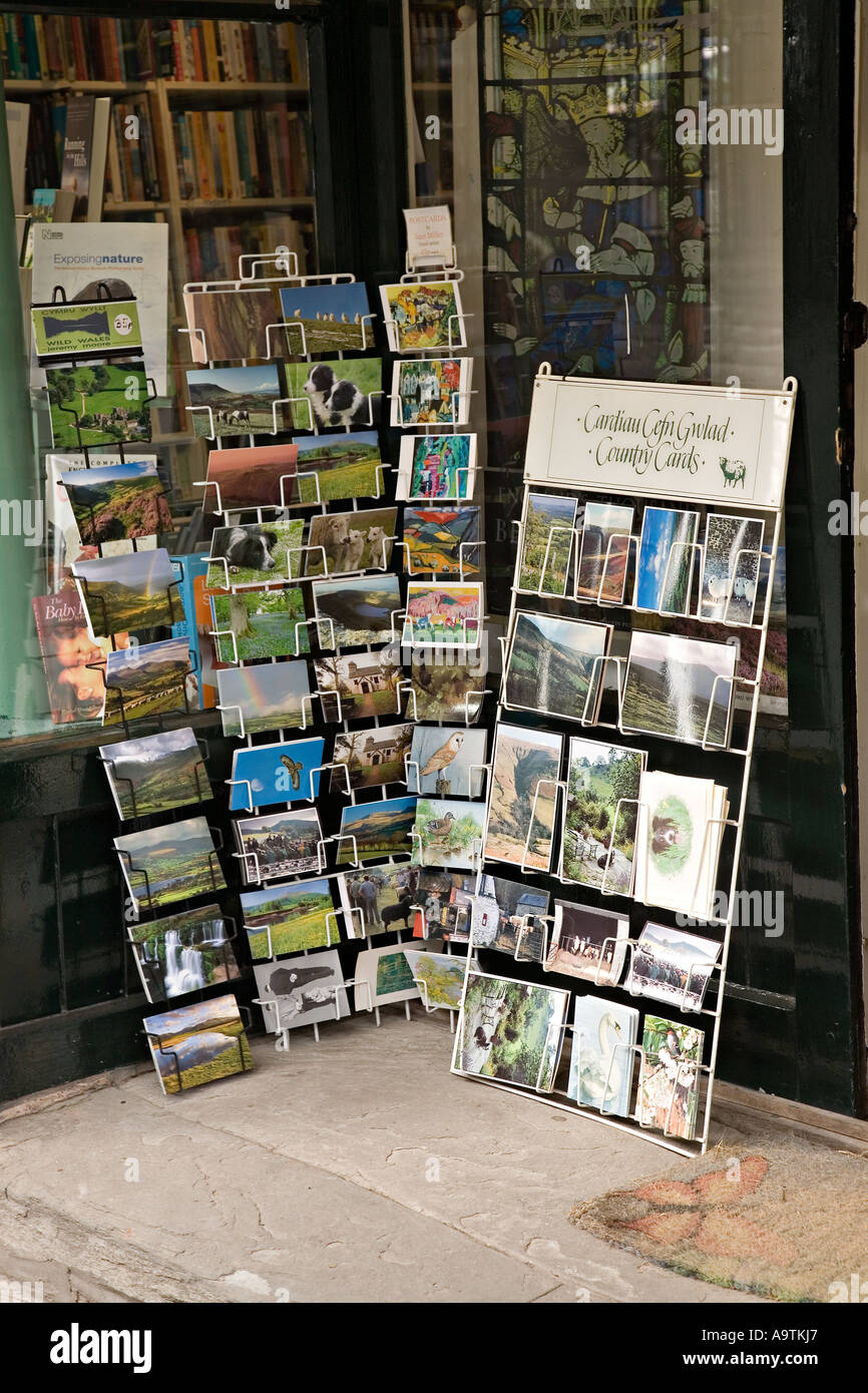 Postcards and greeting cards on sale to tourists in bookshop doorway Hay on Wye Wales UK - Stock Image