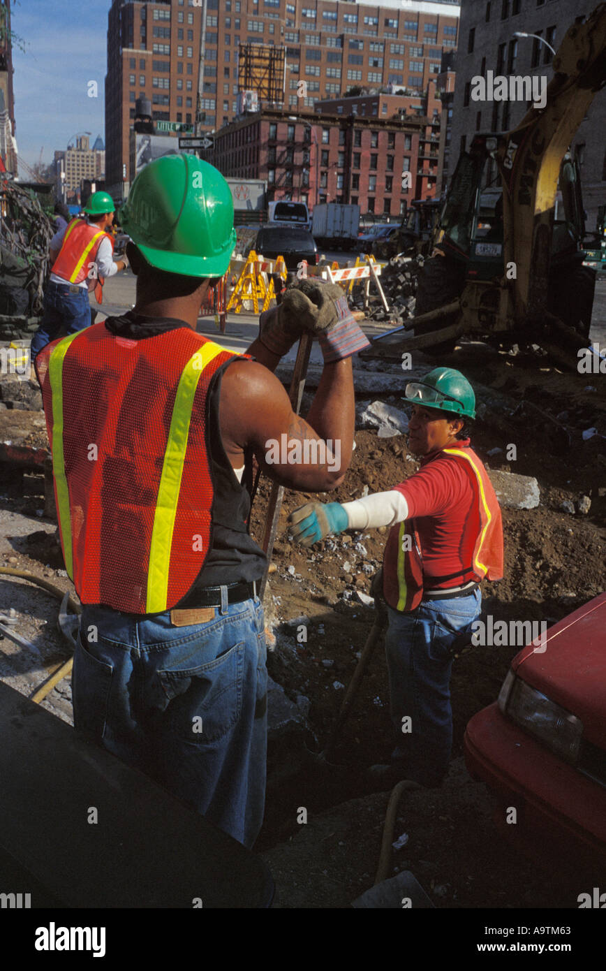 NYC male industrial construction workers installing cable pipe Stock Photo