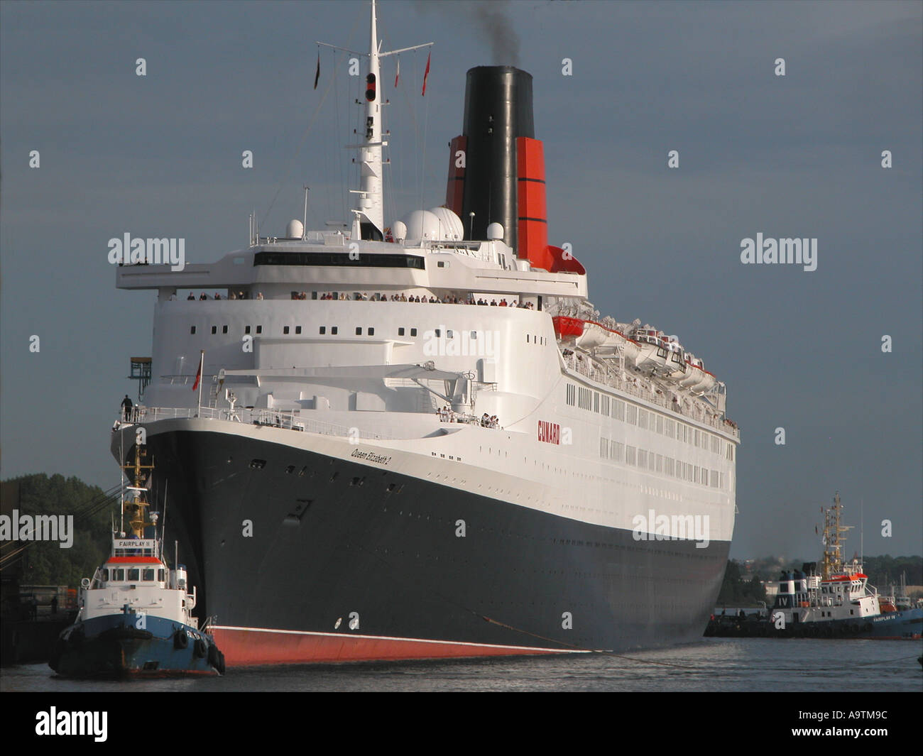 Visit of Liner QE2 to Rostock Germany being towed by tugboats and on baltic cruise - Stock Image