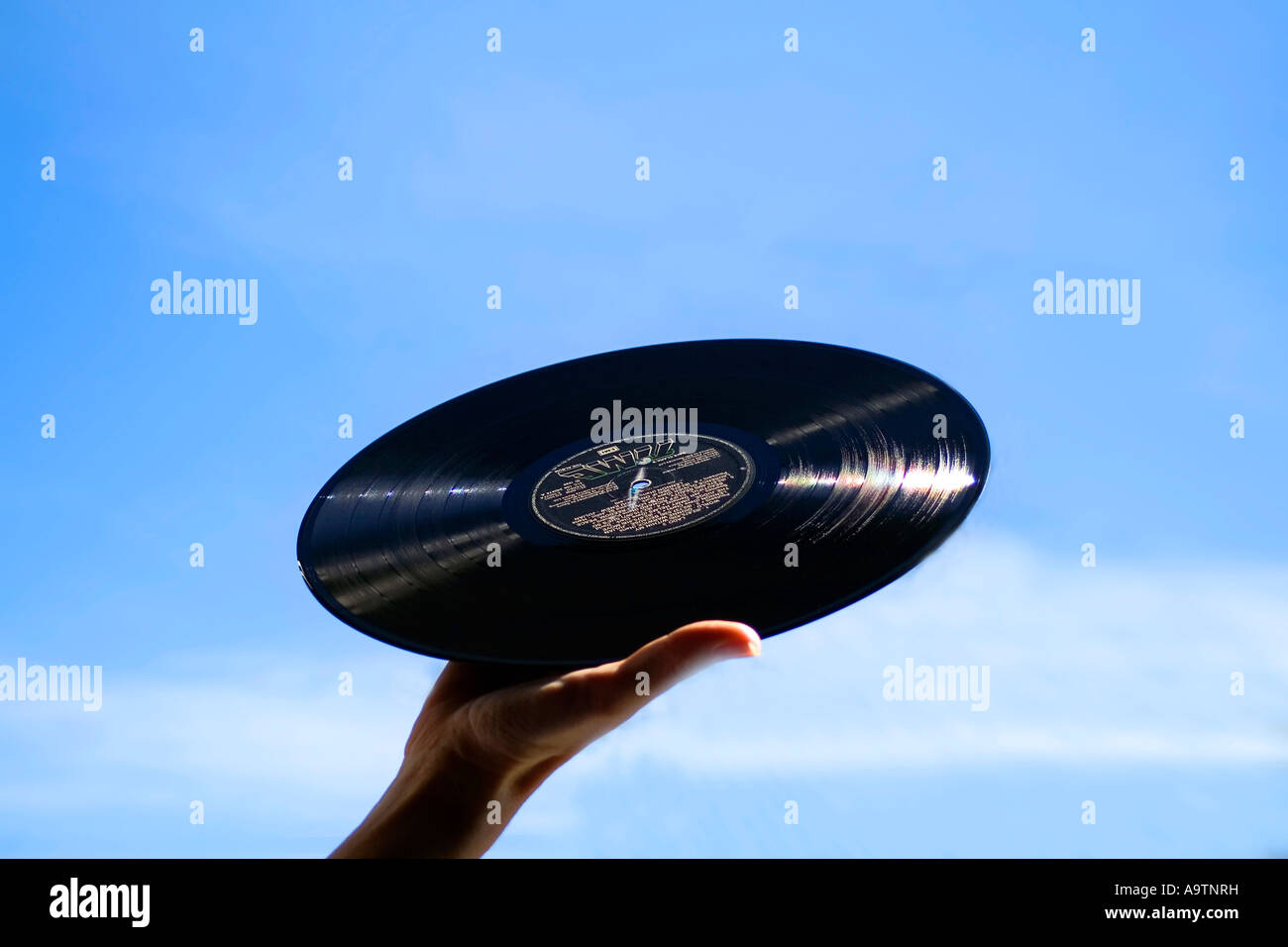 Hand holding Vinyl Record in the air Stock Photo