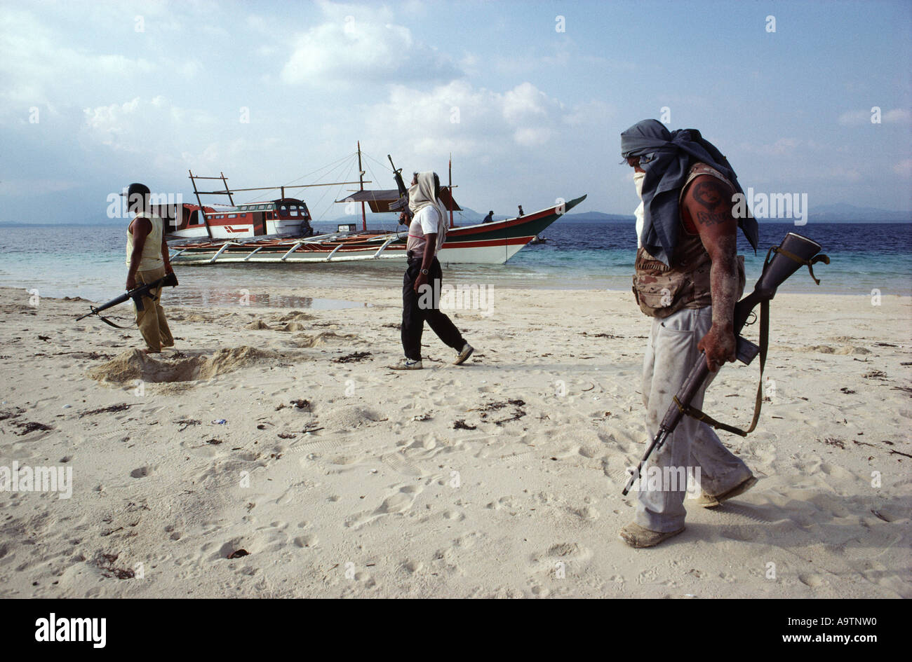 The pirate crew walking along the beach of a shallow sandbar, their boat in the background. - Stock Image