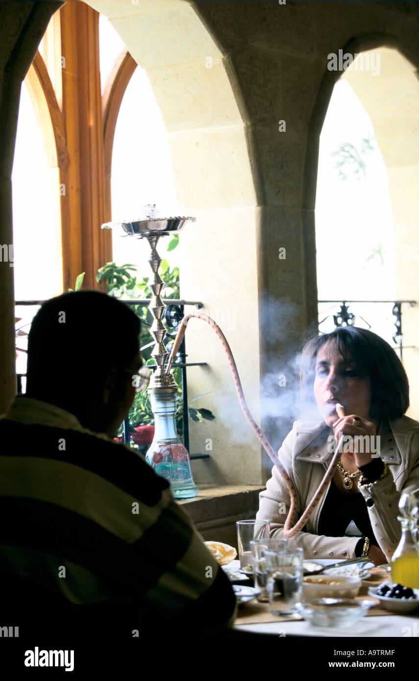 BEIRUT BEIT MERI AREA JDOUDNA RESTAURANT WOMAN SMOKING WATER PIPE DURING LUNCH 1998 Stock Photo