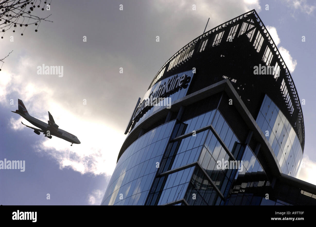 GlaxoSmithKline HQ in UK with passing aircraft - Stock Image