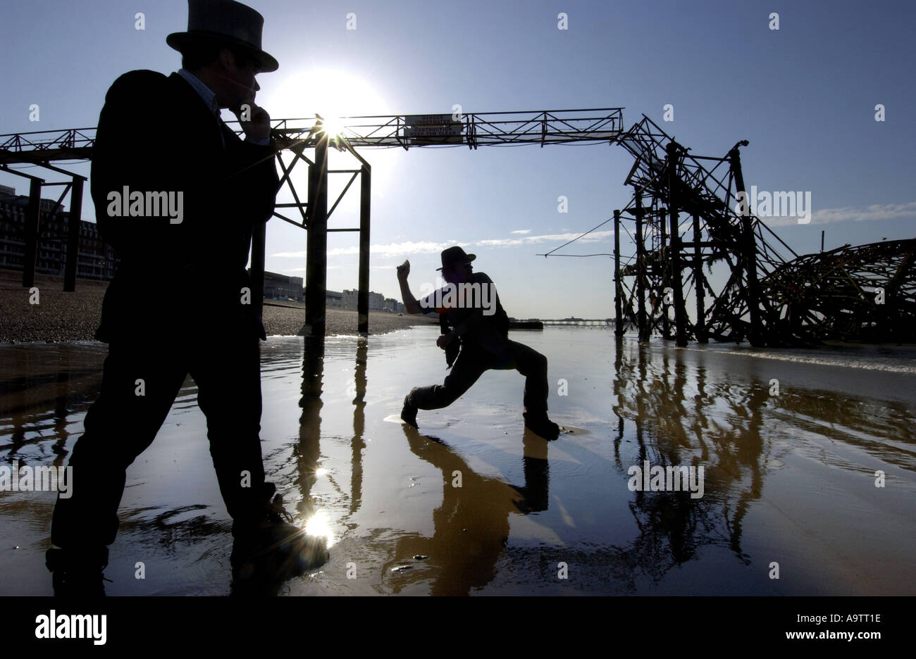 Stone skimming competition on Brighton Beach. A contender lobs a stone, watched by a judge in a top hat Stock Photo