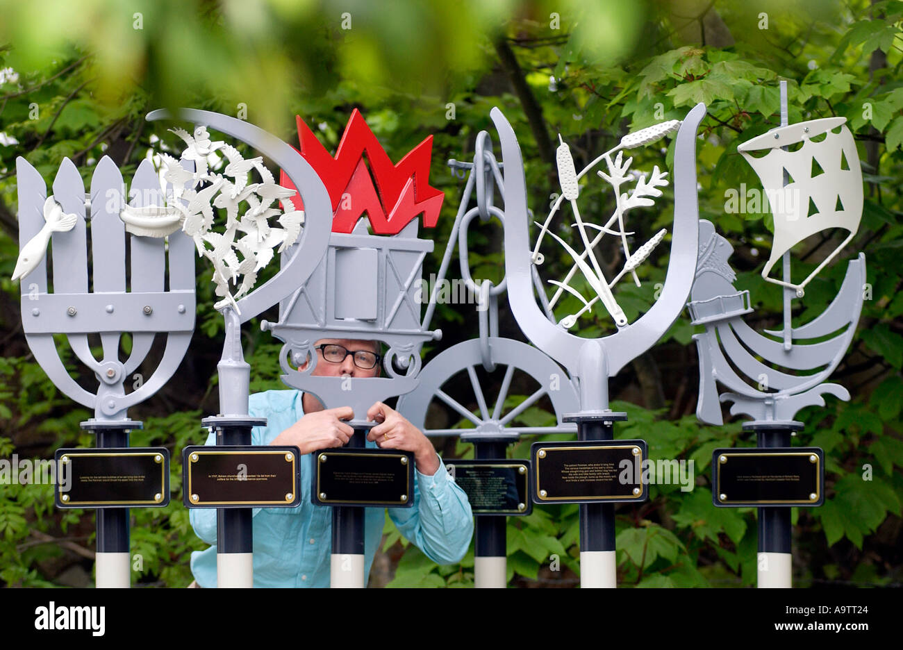 A sculptor with a series of Waymarkers for footpath junctions, commemorating local historical events. - Stock Image
