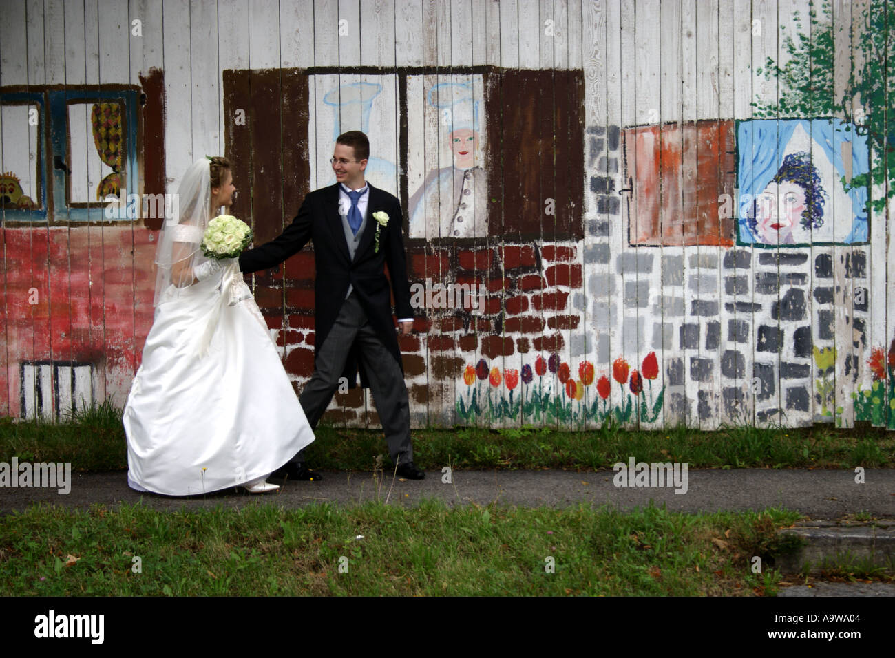 bride and groom in front of Graffiti wall painting Stock Photo