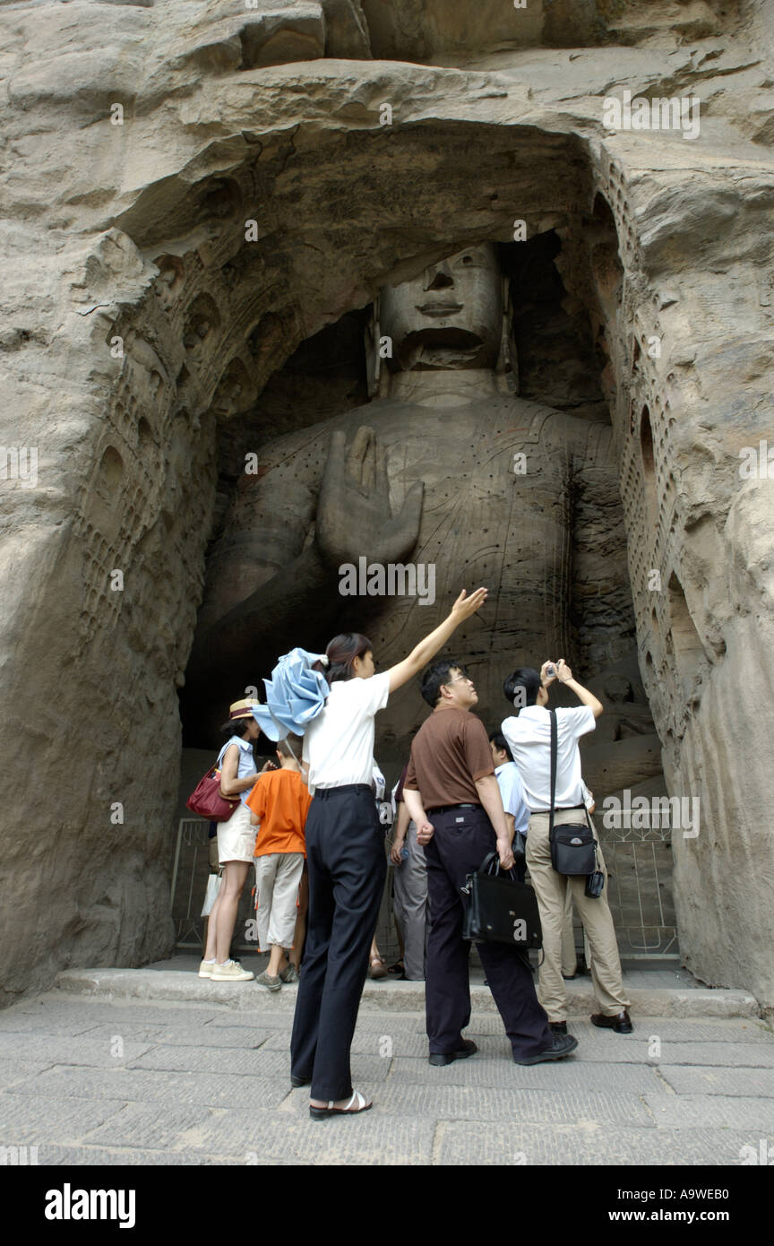 Group Of Chinese Tourists and Guide In Front Of A Giant Buddha Statue Carved Inside The Yungang Shiku Grottoes / Grotto, China - Stock Image