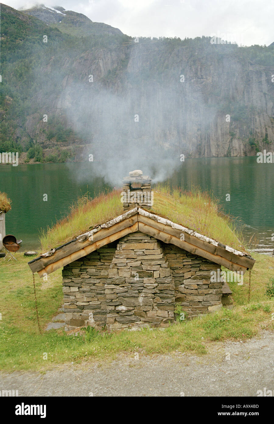 Hut with smoking chimney in Norwegian landscape - Stock Image