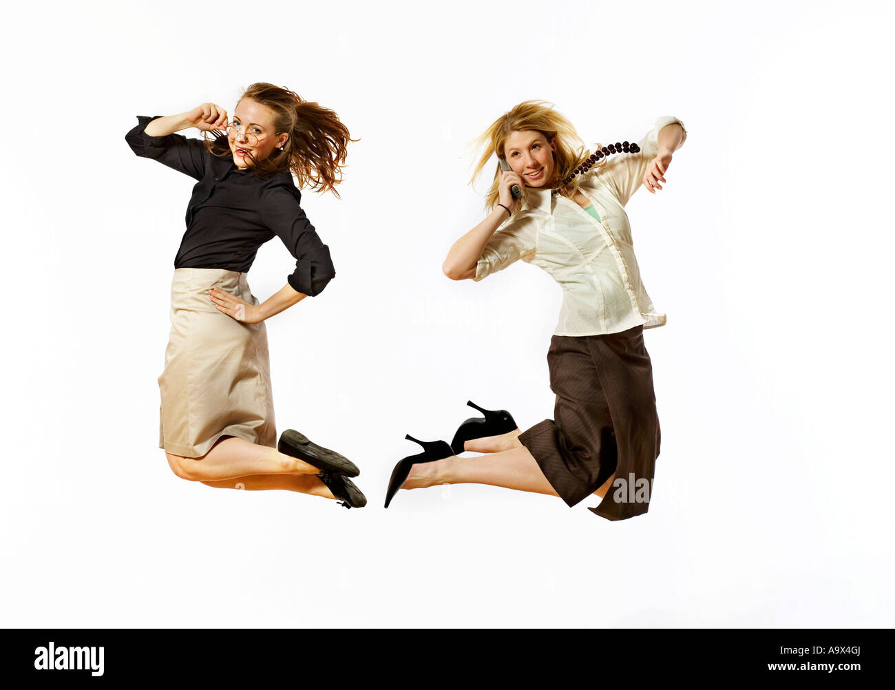 two lovely young women jumping in the air, one holding her glasses, the other with a mobile or cell phone to her - Stock Image
