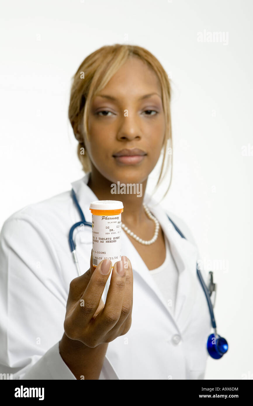 Young female doctor in a white coat holding a jar of pills towards the patient - Stock Image