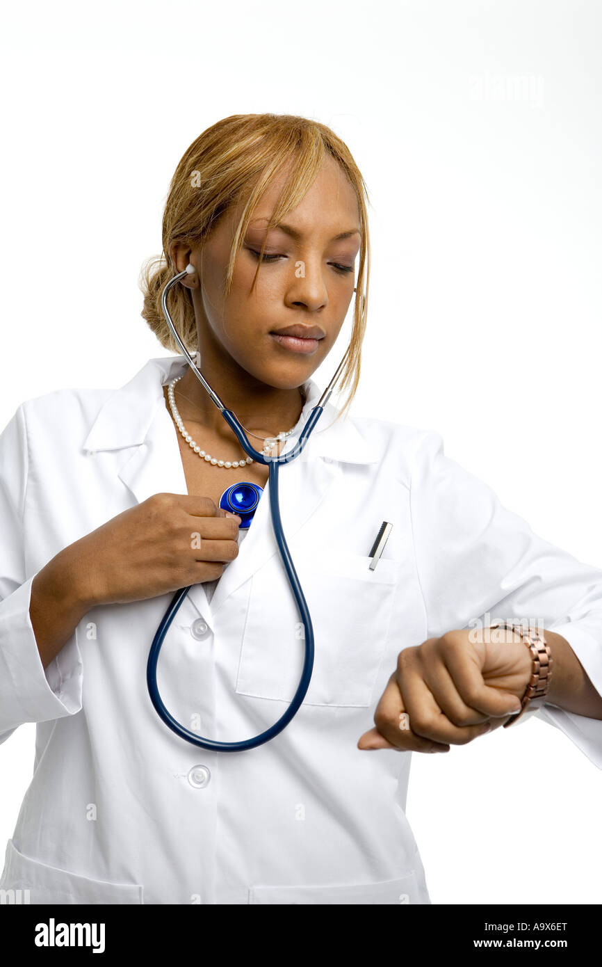 Young female doctor listening to her own heart with a stethoscope while wearing a white coat - Stock Image