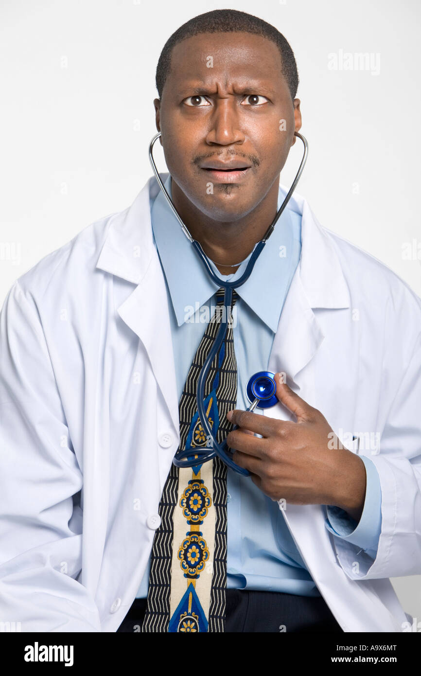 Humorous photograph of a doctor listening to his own heart with a stethoscope making a funny face and wearing a - Stock Image