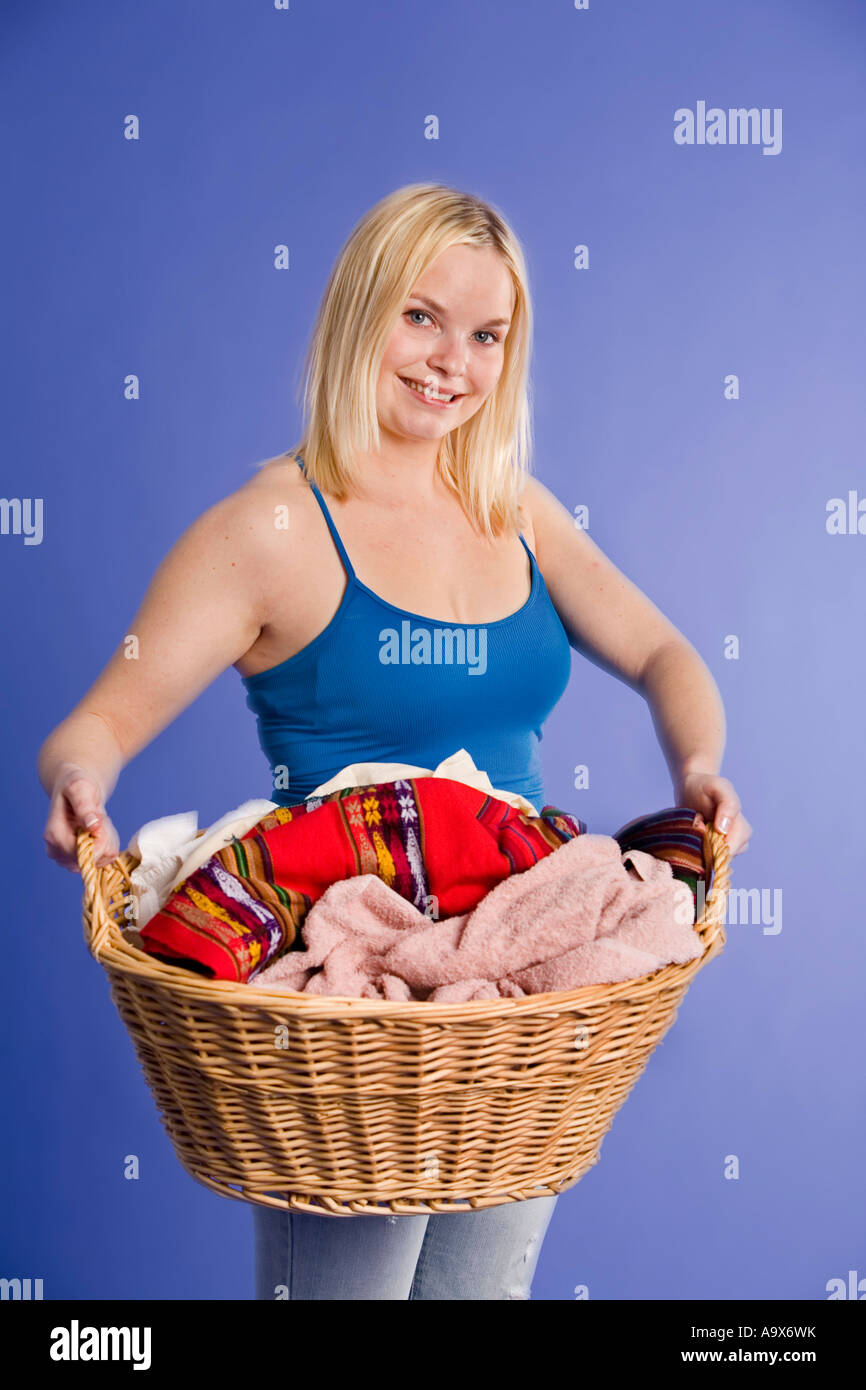 Smiling attractive blonde young woman with a basket of laundry - Stock Image