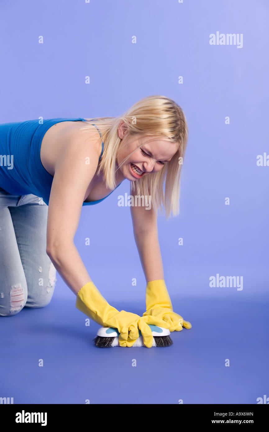 Blonde woman scrubbing a floor - Stock Image