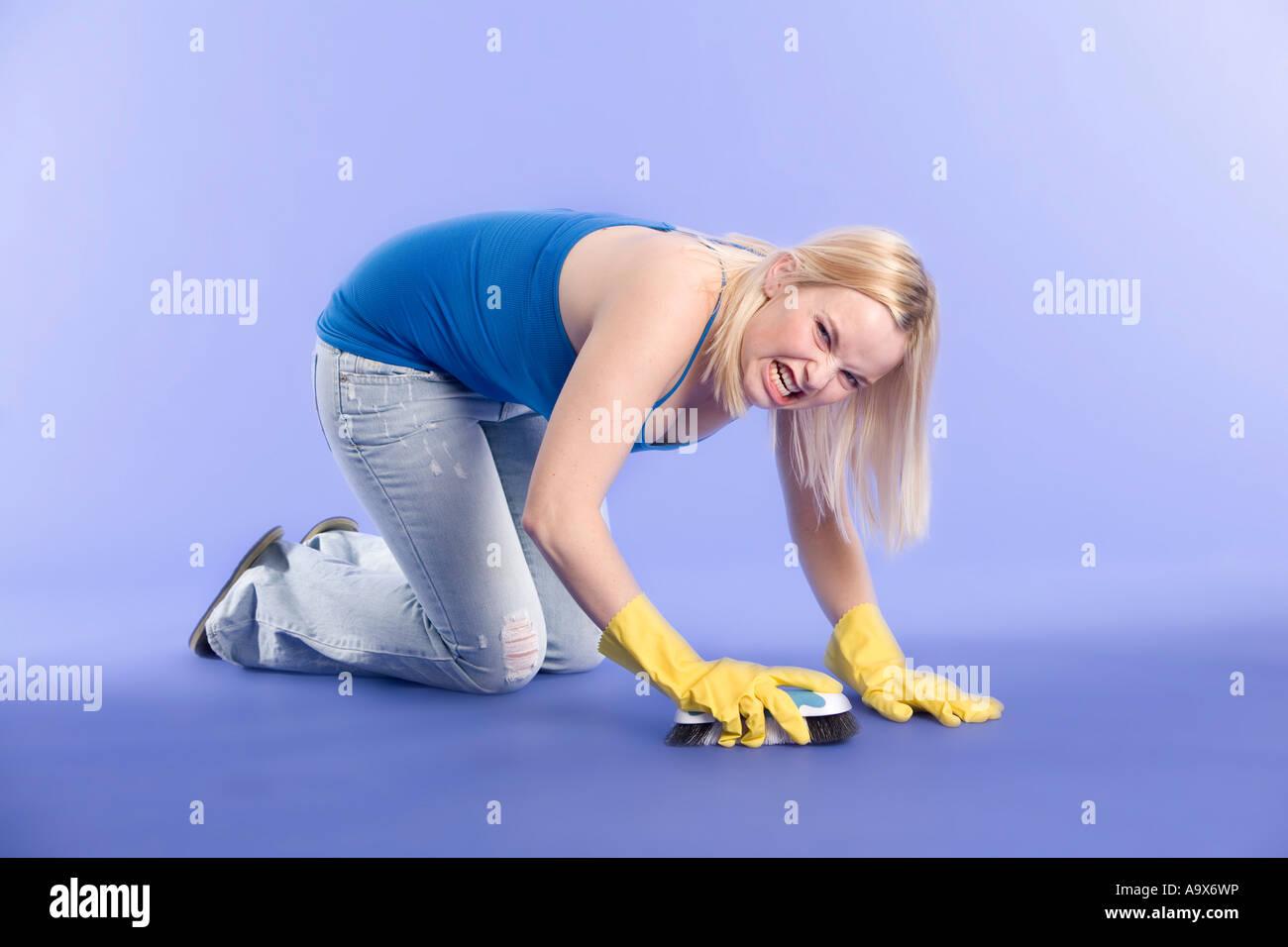 young woman scrubbing a floor unhappily - Stock Image