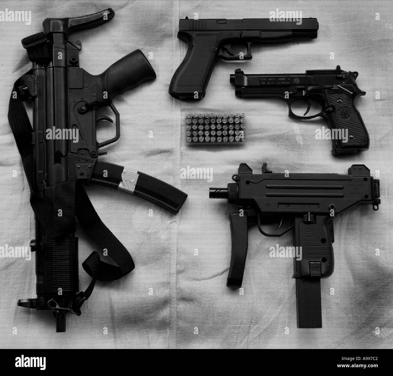 a selection of handguns including an uzi sub machinegun an heckler and koch MP5 machinegun beretta and glock 17L pistols - Stock Image
