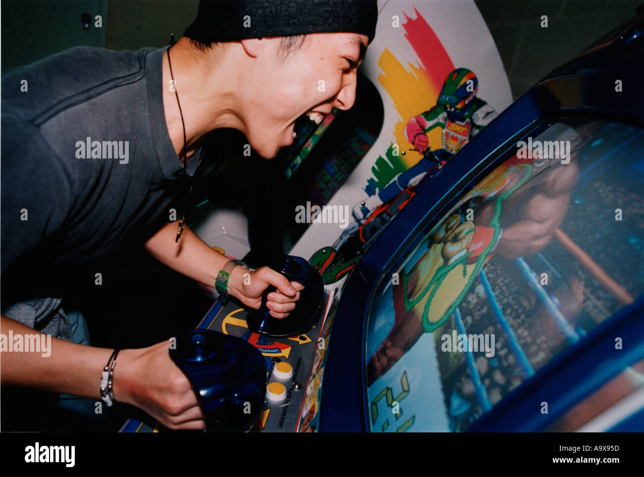 A male youth plays a boxing arcade game - Stock Image