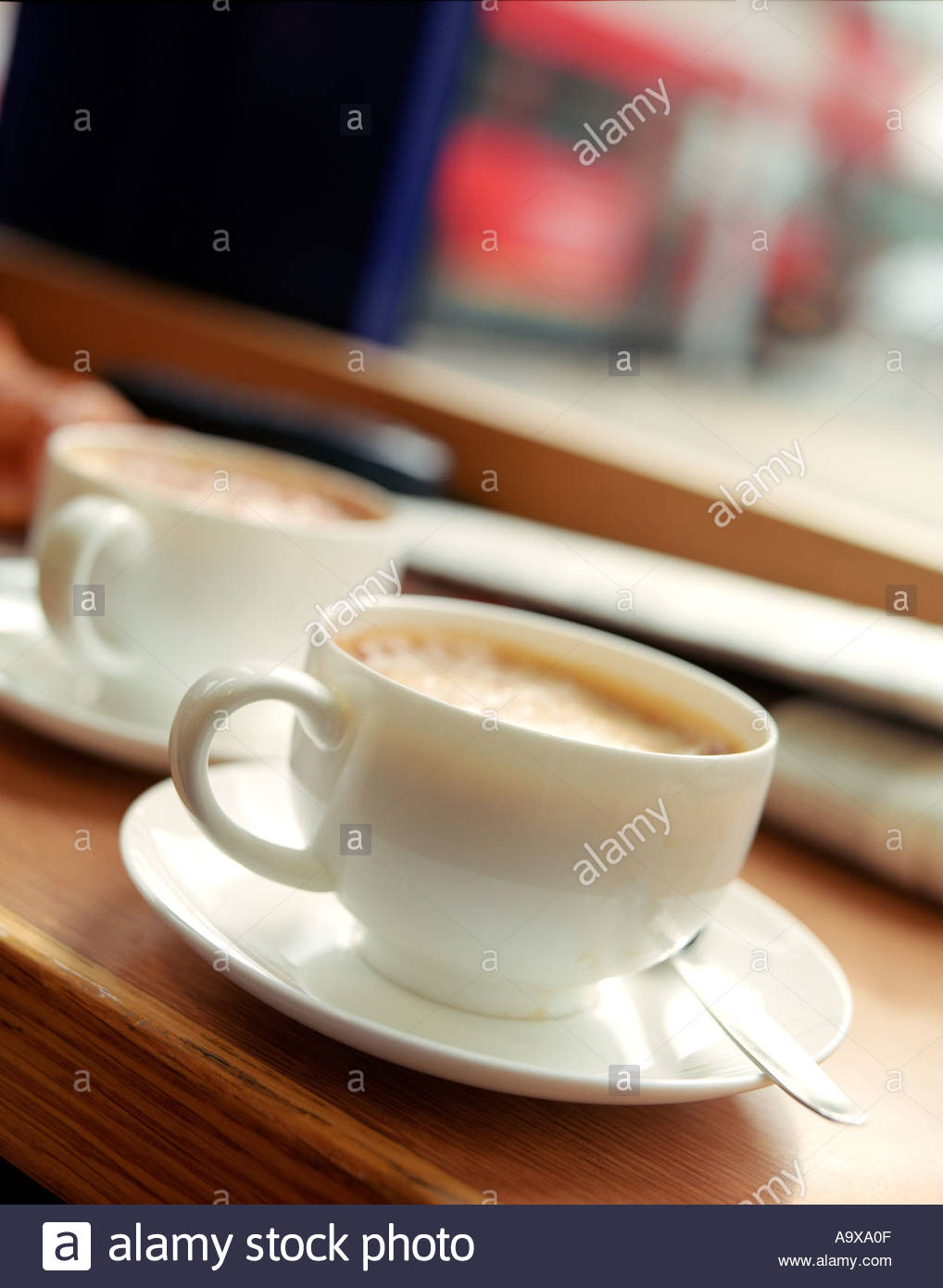detail color coffee cup in window of coffee shop showing life passing the window with a croissant in the background adding depth - Stock Image