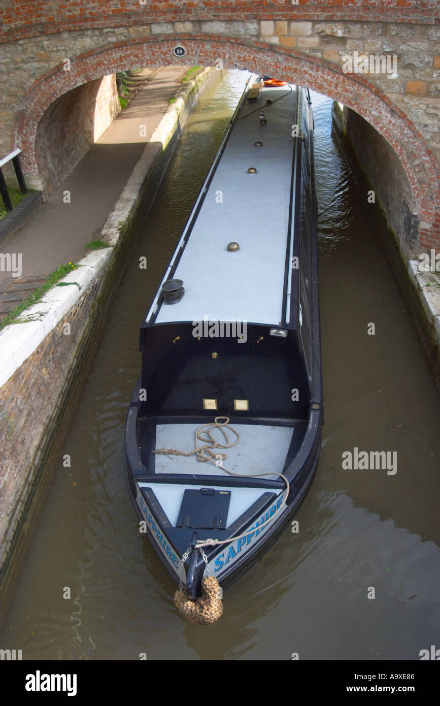 A boat emerging from the locks at Stoke Bruerne on the Grand Union Canal England - Stock Image