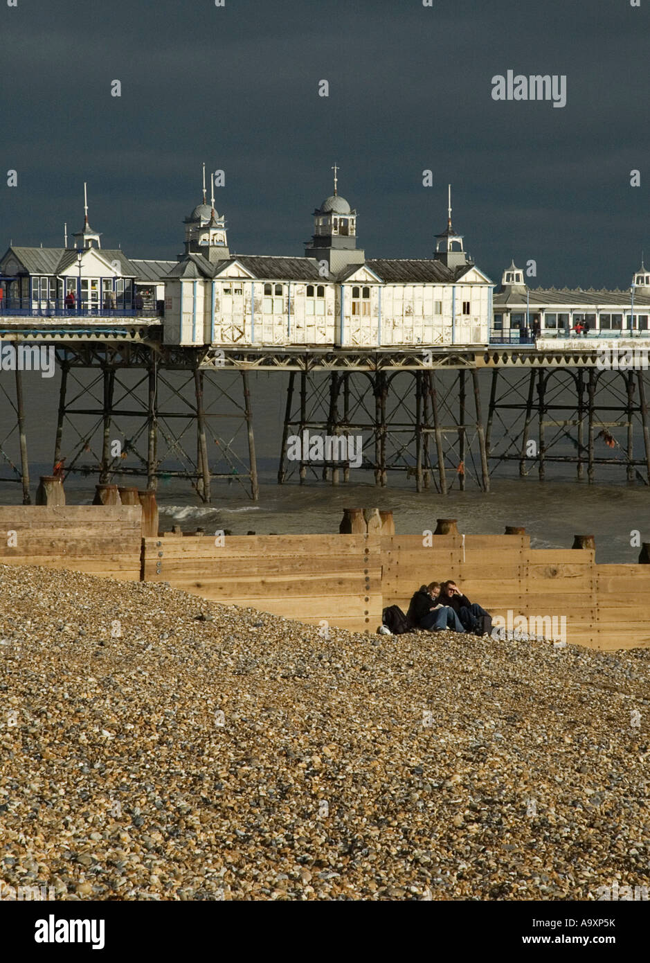 Young couple sheltering on Eastbourne beach, with pier - Stock Image