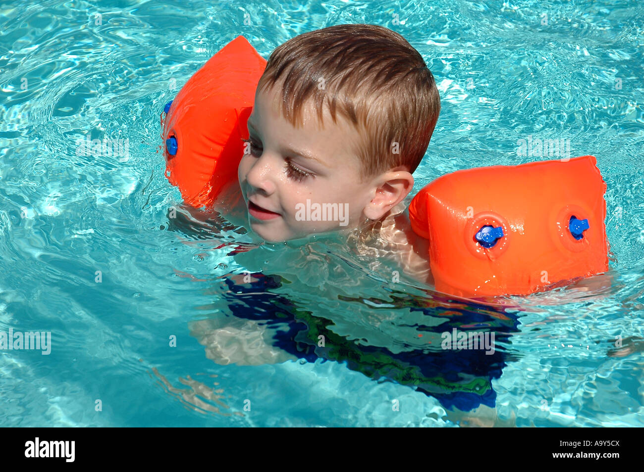 Swimming Pool Wings : Boy with water wings in swimming pool stock photo