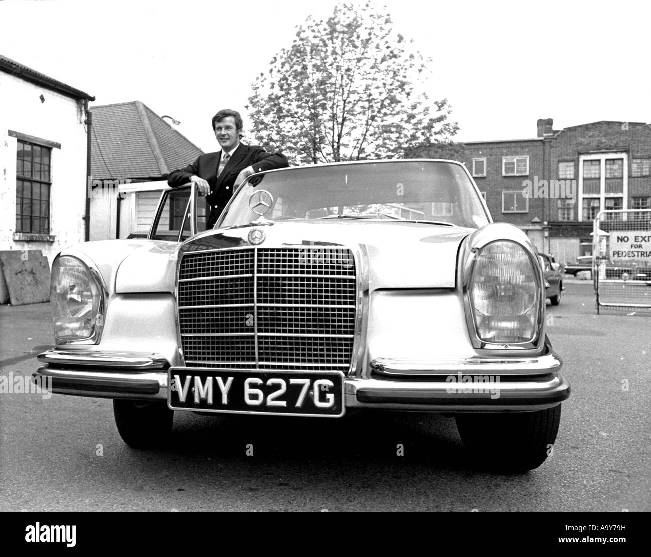 ROGER MOORE with his Mercedes at Elstree Studios, north London, while filming The Saint TV series about 1963 - Stock Image