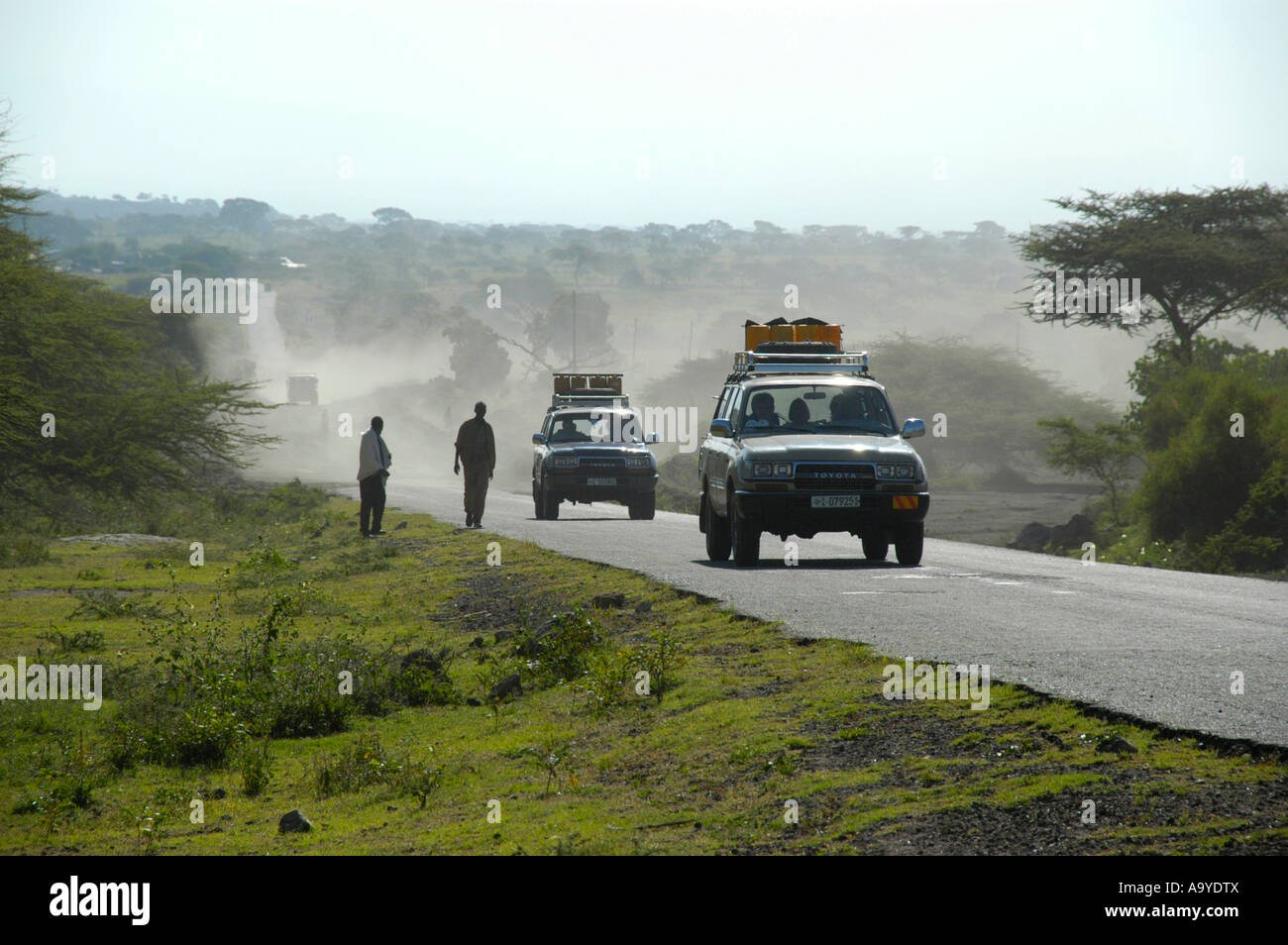 Two Toyota Landcruiser with expedition equipment on a road in the savannah near Shashamene Ethiopia - Stock Image