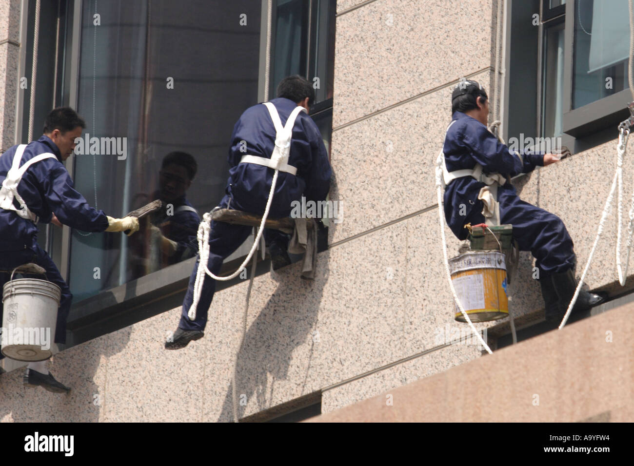 Window washing at Beijing Hotel - washers dangle from ropes - Stock Image